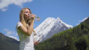 Donna bionda che beve acqua alpina stock footage