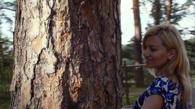 Donna bionda che cammina intorno al pino in parco, vista di rotazione stock footage