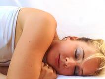 Donna bionda che dorme sul fondo bianco immagine stock libera da diritti