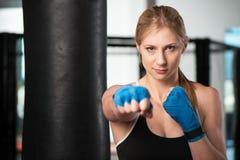Donna bionda che fa allenamento di arti marziali in una palestra Immagine Stock