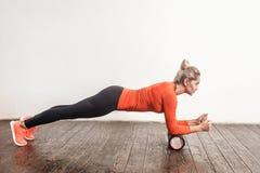 Donna bionda che fa plancia in rullo della schiuma fotografia stock