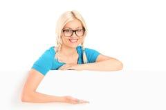Donna bionda che gesturing con la mano dietro un pannello Immagini Stock Libere da Diritti