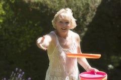 Donna bionda che getta un disco di plastica in un giardino Fotografie Stock
