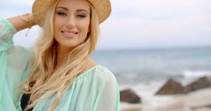 Donna bionda che gode della brezza sulla spiaggia stock footage