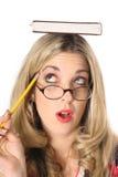 Donna bionda che pensa con il libro sulla testa immagini stock libere da diritti