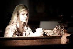 Donna bionda che prega in una chiesa fotografia stock libera da diritti