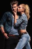 Donna bionda che prova a baciare il suo ragazzo sulla guancia Fotografia Stock