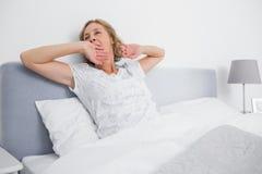 Donna bionda che sbadiglia e che allunga a letto di mattina Immagine Stock