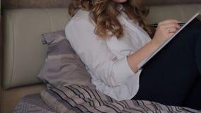 Donna bionda che si siede su un letto di scrittura nera della penna nel taccuino bianco video d archivio