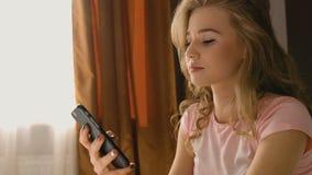Donna bionda che si siede sul letto, tenente il suo telefono in mani e chiacchierante per sentire gli amici in un pigiama rosa stock footage
