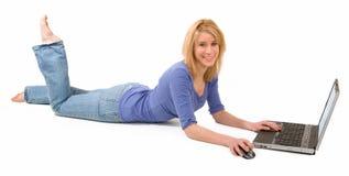 Donna bionda che si trova giù e che per mezzo del computer portatile fotografia stock