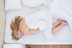Donna bionda che si trova a letto ottenendo mal di stomaco Immagini Stock