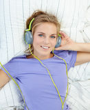 Donna bionda che si trova sul letto mentre musica d'ascolto Fotografie Stock Libere da Diritti
