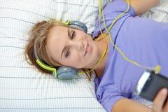 Donna bionda che si trova sul letto mentre musica d'ascolto Fotografia Stock
