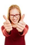 Donna bionda che tiene i suoi pollici su Immagine Stock