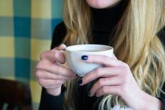 Donna bionda che tiene tazza di tè in un caffè Fotografia Stock