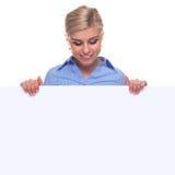 Donna bionda che tiene una scheda di messaggio in bianco. Immagini Stock