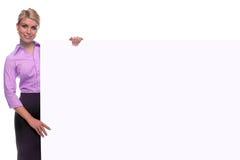 Donna bionda che tiene una scheda di messaggio in bianco. Fotografia Stock