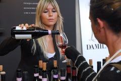 Donna bionda che versa vino rosso dalla bottiglia al vetro del cliente Fotografia Stock