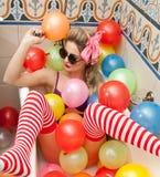 Donna bionda con gli occhiali da sole che giocano in suo tubo del bagno con i palloni colorati luminosi Ragazza sensuale con le c immagine stock