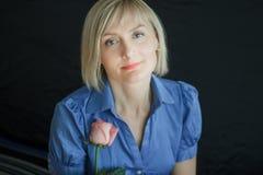 Donna bionda con il ritratto rosa dello studio del fiore Immagine Stock