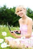 Donna bionda con il suo computer portatile fra le margherite Immagine Stock