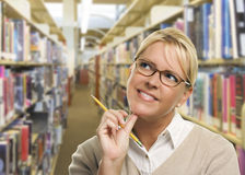 Donna bionda con la matita che guarda al lato in biblioteca Fotografia Stock Libera da Diritti