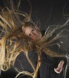 Donna bionda con vento che soffia tramite i capelli lunghi Immagine Stock