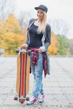 Donna bionda d'avanguardia splendida con un bordo del pattino Fotografia Stock