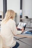 Donna bionda dell'ufficio al suo scrittorio che legge un libro Fotografia Stock