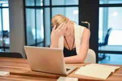 Donna bionda di affari depressi che ha difficoltà con i suoi impianti Immagini Stock Libere da Diritti
