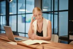 Donna bionda di affari depressi che ha difficoltà con i suoi impianti Immagini Stock