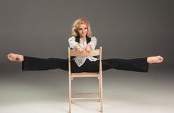 Donna bionda di bellezza sulla sedia nella posa di balletto Immagini Stock Libere da Diritti