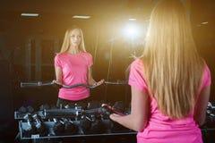 Donna bionda di forma fisica in abiti sportivi con l'ente perfetto che posa nella palestra Ragazza sportiva attraente che riposa  Fotografia Stock