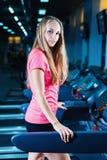 Donna bionda di forma fisica in abiti sportivi con l'ente perfetto che posa nella palestra Ragazza sportiva attraente che riposa  Fotografie Stock Libere da Diritti