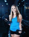 Donna bionda di forma fisica in abiti sportivi con l'ente perfetto che posa nella palestra Ragazza sportiva attraente che riposa  Fotografie Stock