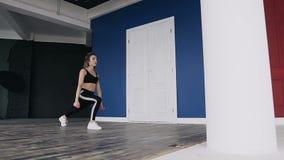 Donna bionda di forma fisica attraente che fa allenamento con le teste di legno rosa in sue mani, nella palestra Si è vestita nel archivi video