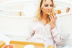 Donna bionda di giovane bellezza che ha mattina soleggiata in anticipo della prima colazione a letto, stanza interna della casa d fotografie stock libere da diritti