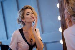 Donna bionda di lusso di bellezza Giovane modello attraente in bello vestito che si siede davanti allo specchio, per vestiresi el Immagine Stock Libera da Diritti