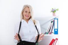 Donna bionda di mezza età adorabile con un sorriso di orientamento che si siede all'ufficio che esamina la macchina fotografica immagine stock