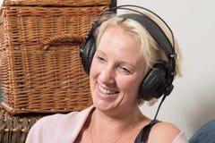 Donna bionda di seduta nelle inclinazioni testa e sorrisi delle cuffie Fotografia Stock Libera da Diritti