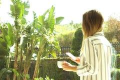 Donna bionda di Unrecognizible che per mezzo dello smartphone, bevente il suo caffè di mattina dalla tazza bianca Chiuda su sulle fotografia stock