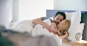 Donna bionda ed uomo che sorridono, abbraccianti ed addormentati Le coppie nella mattina di amore svegliano a casa in camera da l archivi video