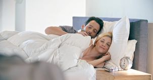 Donna bionda ed uomo che sorridono, abbraccianti e riposanti Le coppie nella mattina di amore svegliano a casa in camera da letto archivi video