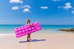 Donna bionda esile con la spiaggia di tropico del materasso di aria immagine stock