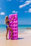 Donna bionda esile con la spiaggia di tropico del materasso di aria fotografie stock libere da diritti