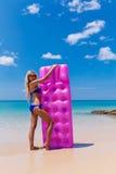 Donna bionda esile con la spiaggia di tropico del materasso di aria fotografia stock