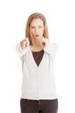 Donna bionda felice che indica su voi Fotografia Stock