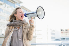 Donna bionda felice che parla sul megafono Immagini Stock Libere da Diritti