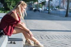 Donna bionda felice che si siede sui punti sulla via che indossa un rosso Immagine Stock